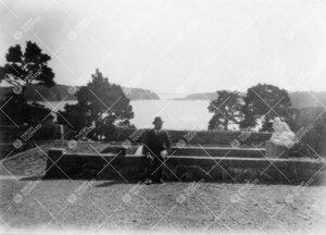 Kultarannan puutarhaa 1920-luvun alussa. Mies, kiveystä ja  veistos. Taustalla meri. (Kirjaston vä