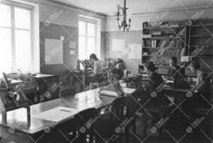 Työn touhussa fysiikan laitoksella 1940-luvun jälkipuolella.  Opiskelija ikkunan edessä mittaa (t