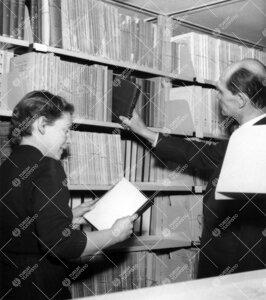 Ylikirjastonhoitaja Eero K. Neuvonen ja anon. pääkirjaston  kirjavarastossa 1950-luvun puolivälis