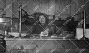 Nuor. alikirjastonhoitaja Kerttu Rautaniemi työpöytänsä ääressä  kirjaston lukusalissa Phoeni