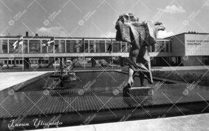 Keskusaukio. Näkymä Genius-patsaan ja suihkualtaan takaa kohti  kahvilaniveltä ja päärakennusta