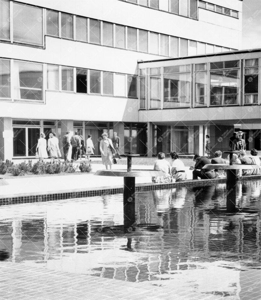Opiskelijoita 1950- ja 1960-lukujen vaihteen aikaan suihkualtaan  reunustalla ja Luonnontieteidental
