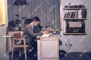 Asukas tyypillisesti kalustetussa (kirjoituspöytä, tuoli,  kirjahylly) opiskelija-asunnossaan Ylio